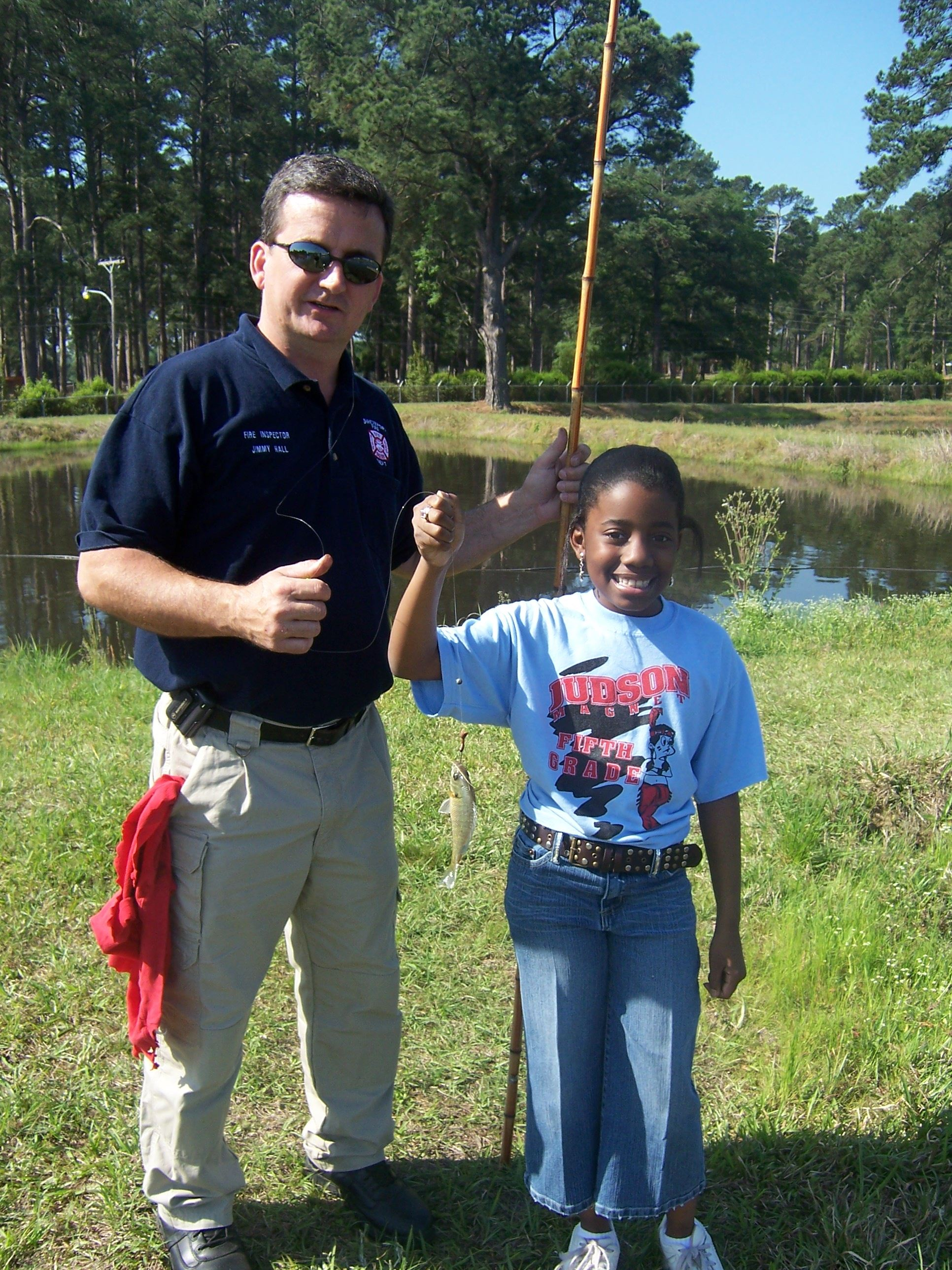 A young girl holding up a fish while standing next to a man